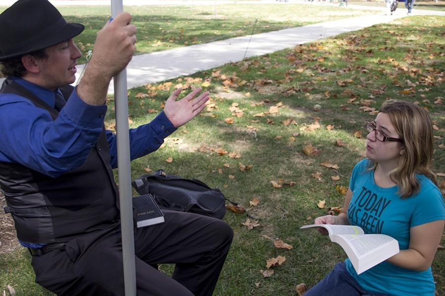 """Tori Coffman, a freshman philosophy major and a member of the Wesley Foundation, reads and discusses Bible verses to Reverend Ryan Simpkins, a reverend from The Christian Ministry USA, on Monday in the Library Quad. """"When you talk to them on the side, they're far less agressive,"""" Coffman said, """"when they're standing up on that block they like to yell and it's mostly for show."""""""