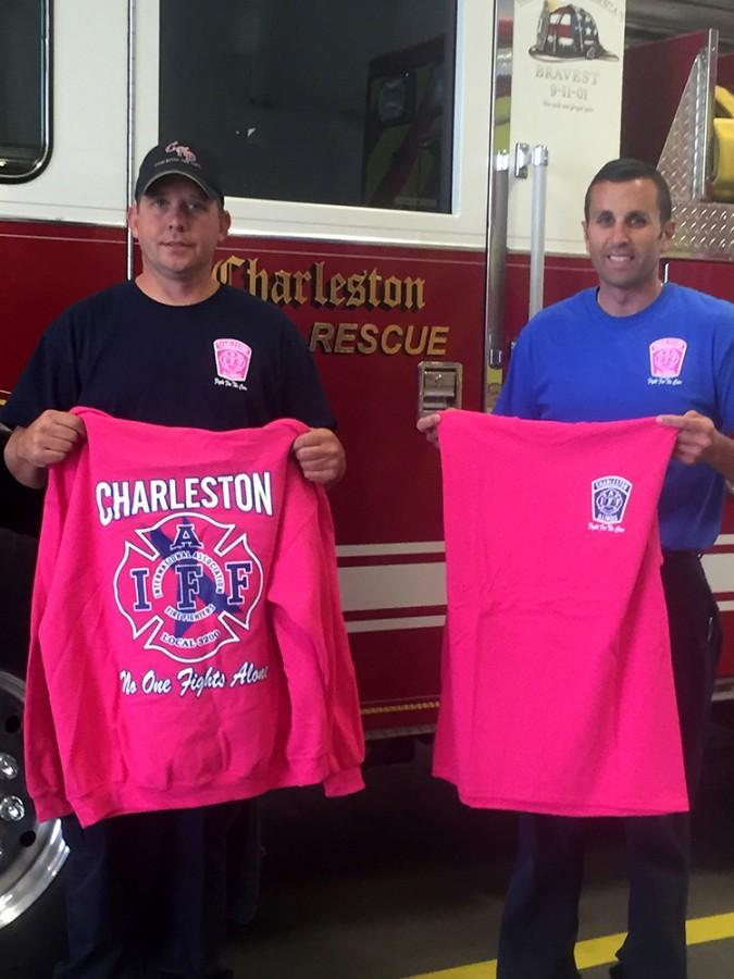Jason Armstrong, a firefighter and paramedic, and Cire Captain Tim Meister hold up examples of what the shirts look like while standing in front of one of the firetrucks at the Charleston Fire Department.