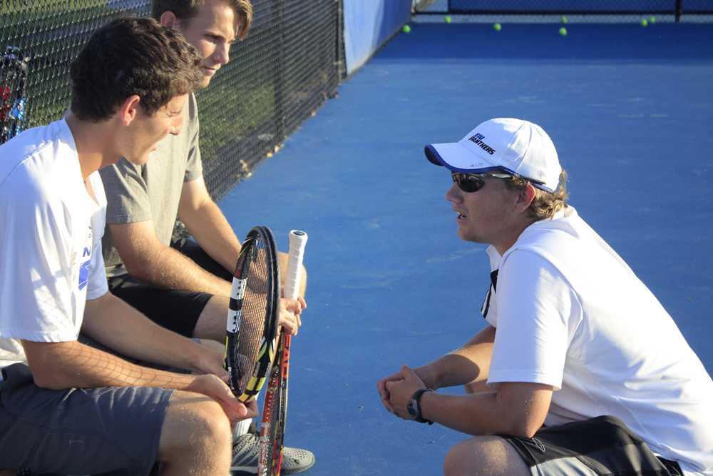 Men's tennis coach, Sam Kercheval speaks with senior players Rui Silva (left) and Ryan Henderson (right) during practice last Wednesday at Darling Courts.