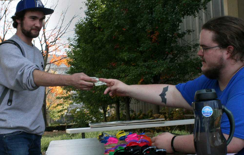 """Mathew Hilliard, a sophomore pholsophy major, pays a dollar for an """"inspirational wristband"""" with the words """"Believe in yourself"""" written on it between Lumpkin and Coleman Hall. Half of the revenue from these rubber bracelets will go to the Illinois Suicide Prevention Resource Center and the other half will go to the entrepreneurship club, the student organization that provided the funds for this entrepreneurship class assignment, said Layne Taylor (right), a junior marketing major, who will be one of the students selling these wristbands 2-4 pm next Tuesday and Thurday in the same location."""
