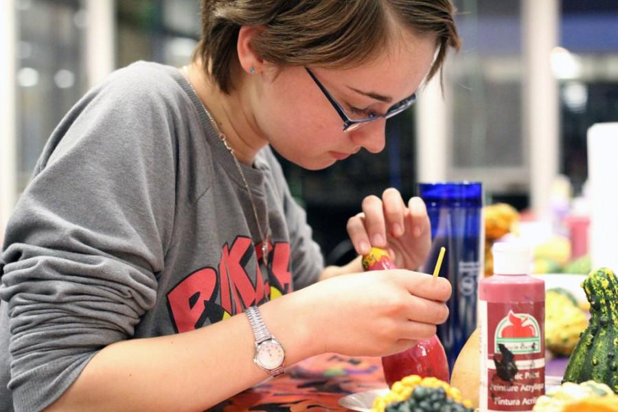 Lauren Eberle, a freshman undecided major, paints squashes during the Taylor Halloween event on Oct. 30, 2014 in Taylor Hall.