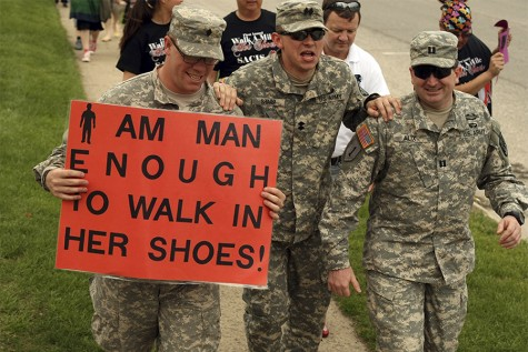 Nick Fetrell and Dan Alix hold their fellow ROTC member, Craig Sharp as he struggles to complelte a mile in heels during Walk a Mile in Her Shoes Sunday. ROTC was a sponsor of the event, which was hosted by Sexual Assault Counseling and Information Servies (SACIS) on April 27, 2014.