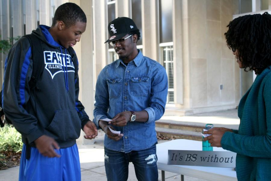 Arius O'Neal, a junior family and consumer sciences major, and Jerome Hampton, a sophomore business management major, pass out little cards advertising the Black Student Union on Monday outside of Coleman Hall. BSU meets Mondays at 6 p.m. in the Charleston/Mattoon Room in the Martin Luther King, Jr. University Union.