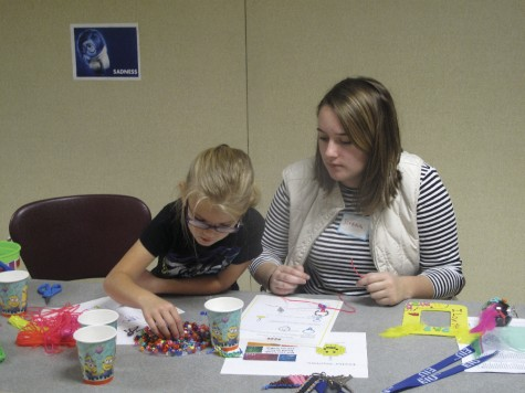 "Jordan Bess, a freshman elementary education major, and Haydyn Thornton, 7, make characters out of beads Saturday morning at ""Kid's Day Out"" in Buzzard Hall."