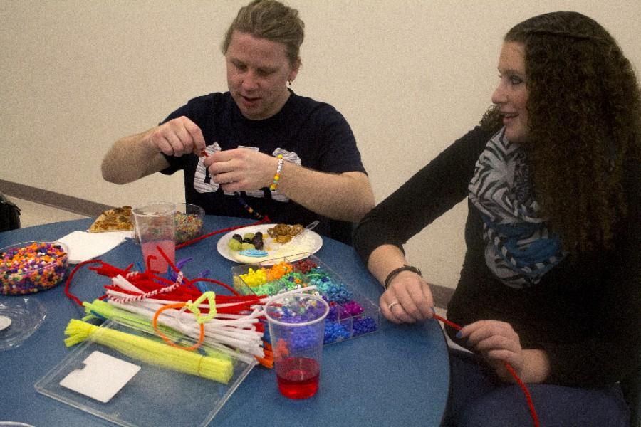 Heather Gebke, a sophomore communication disorders and sciences major, makes beaded braclets and neckless with her Best Buddy, Bret Hackett, a Charleston resident, during the Best Buddies Thanksgiving Dinner on Sunday in the basement of Lawson Hall.