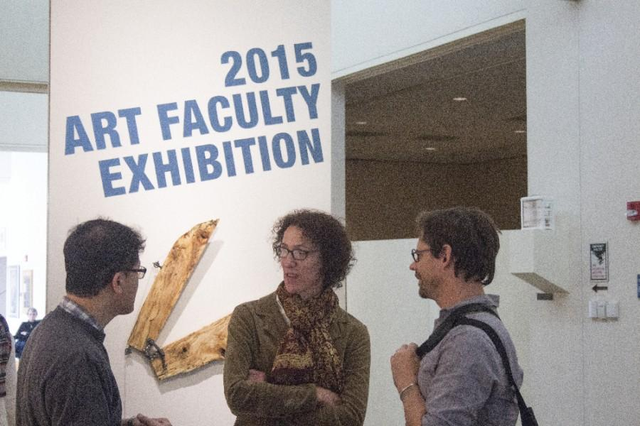 Ann B. Coddington, associate professor of art (center) speaks with Tarble's assistant director Mike Schuetz (right) and  Bo Kim (left), a painting and drawing instructor during 2015 Art Faculty Exhibition Thursday in the Tarble Arts Center.