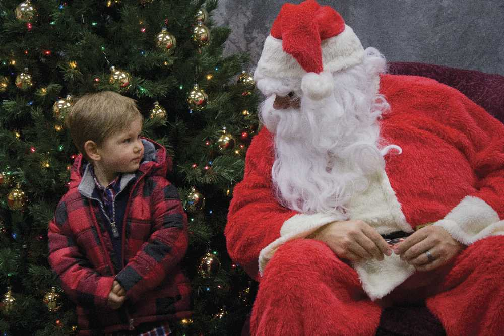 2-year-old Dean Hazelrigg, whose father Todd Hazelrigg is a junior physics major, stands next to Santa for a picture last Saturday at the Festival of Trees.