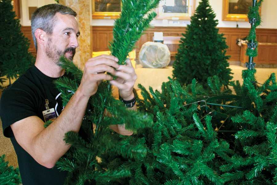 Jarrod Harden, a campus carpenter, sets up the Christmas tree in Old Main on Wednesday. He and his co-worker Johnny Morton have been doing this together for five years.