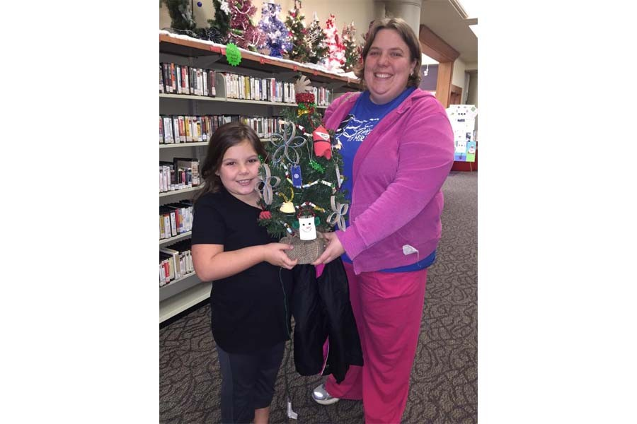 Mother and daughter decorate a christmas tree for the Charleston Carnegie Public Library silent auction.