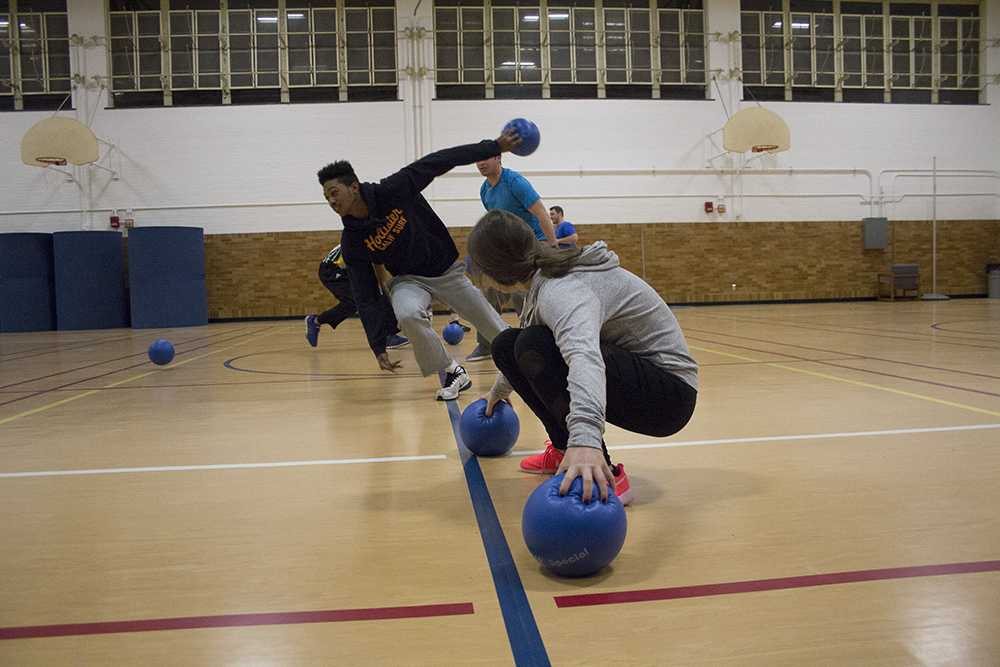 """The first two teams grab the balls after the first round of the """"It's On Us"""" dodgeball tournament Thursday in McAfee Gym."""