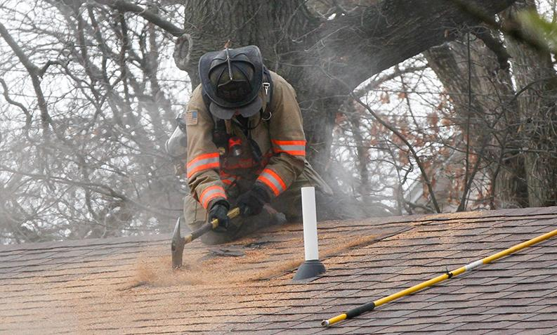 A+member+of+the+Charleston+Fire+Department+uses+an+axe+to+vent+the+roof+while+responding+to+a+fire+at+1015+4th+Street+on+Friday.