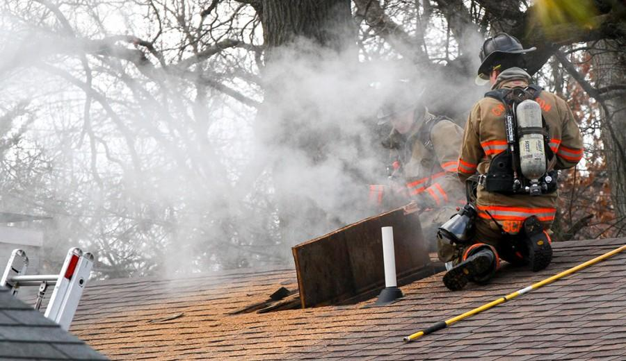 Members of the Charleston Fire Department vent the roof while responding to a fire at 1015 4th Street on Friday.