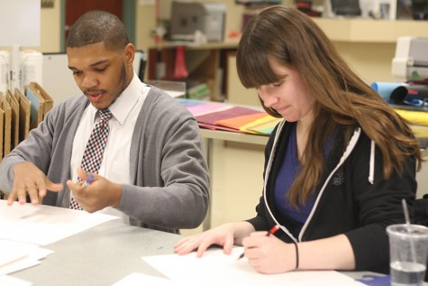 Akeem Forbes, a junior English major and Autumn Frykholm, a junior English major make signs for the rallies in Springfield in the ITC lab Tuesday evening.
