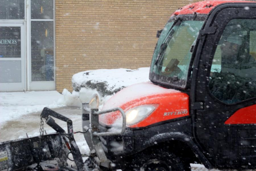 An Eastern groundskeeper plows snow next to the Biological Sciences building on Wednesday. The snow and wind is expected to subside as the day goes on.