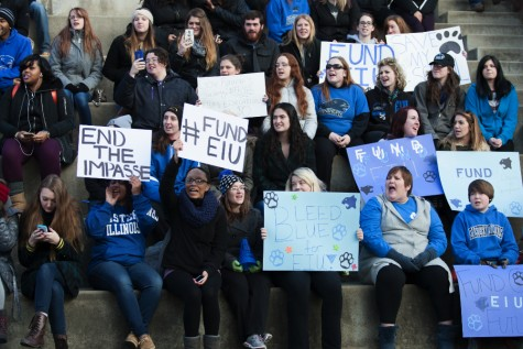 Ralliers hold up signs and chant on the steps of the Doudna Fine Arts Center during the Fund EIU rally on Friday.