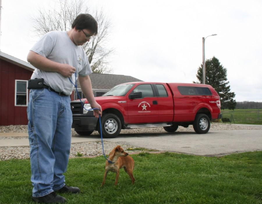Coles County Animal Shelter employee Jason Wallace walks a dog on March 31.