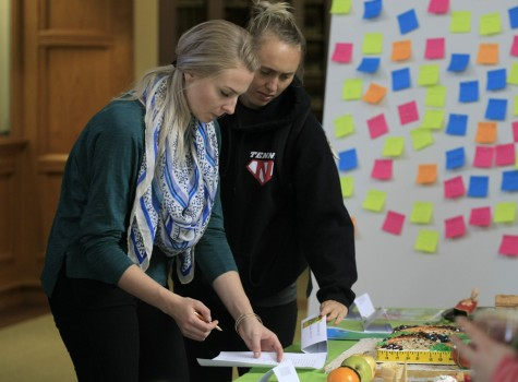 Erin Sutherland along side Alex Curtis, both senior family and consumer sciences majors, vote for their favorite edible book on Monday in Booth Library for the Edible Book Festival.
