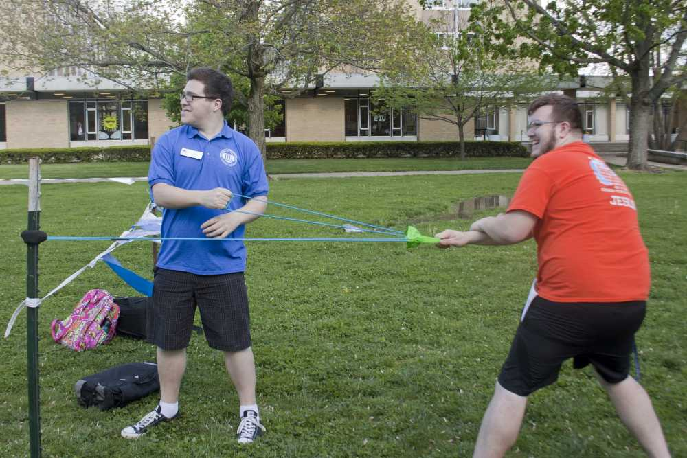 José Durbin, a senior political science major, slingshots a balloon with paint in it during the