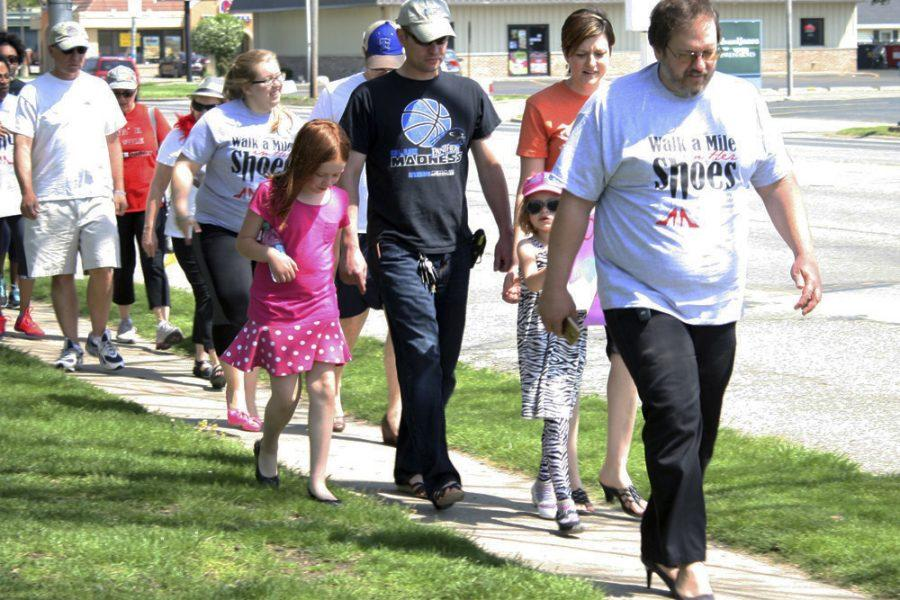 """Participants of the """"Walk a Mile in Her Shoes"""" event march down Lincoln Avenue to raise awareness of sexual assualt and sexual violence Sunday afternoon."""