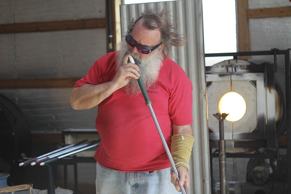 Randy Turner with a metal pipe during his glass blowing workshop on Saturday in Paris.