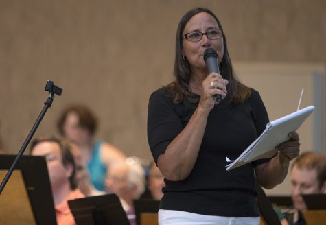 Ginger Stanfield, the director of the Charleston Community Band, introduces the next selection Thursday during the band's concert at Kiwanis Park. Stanfield started participating in this musical group in 1979, two years after it was started.