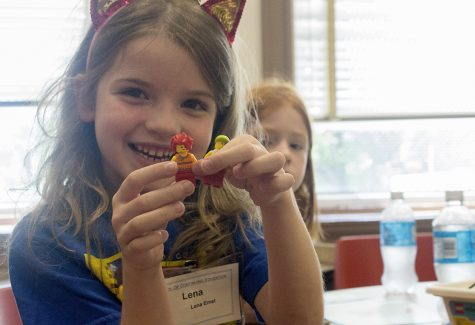 """A camper shows off the LEGO people she assembled Monday during the """"Beginning Engineering LEGO Camp"""" in room 2221 of Old Main. The project of the day was a merry-go-round, which involved a crank and a turntable."""