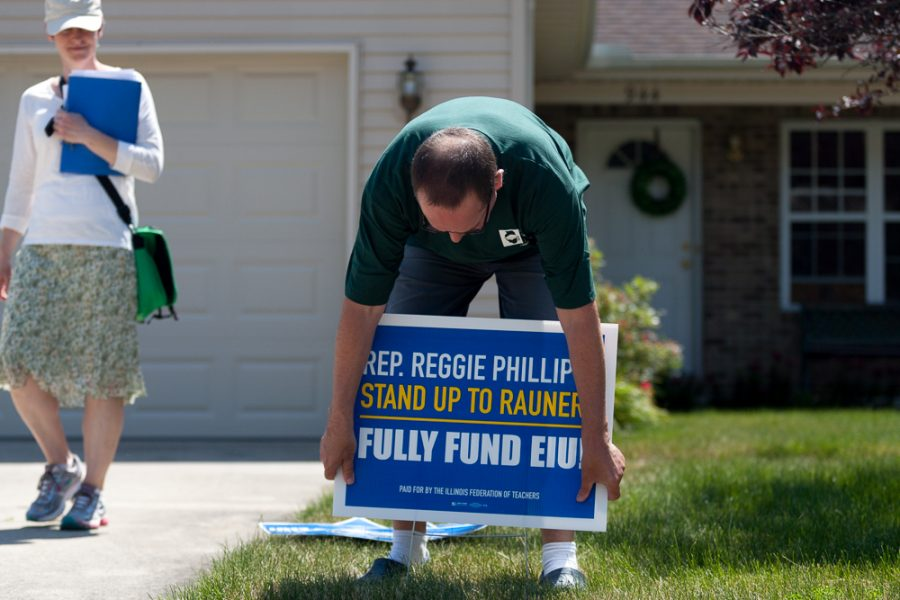 Stefan Eckert, a music professor, places a sign in a yard on Briarwood Court in Charleston on Saturday. Eckert was accompanied by Sace Elder, a women's studies professor and member of the EIU-UPI mobilization committee.