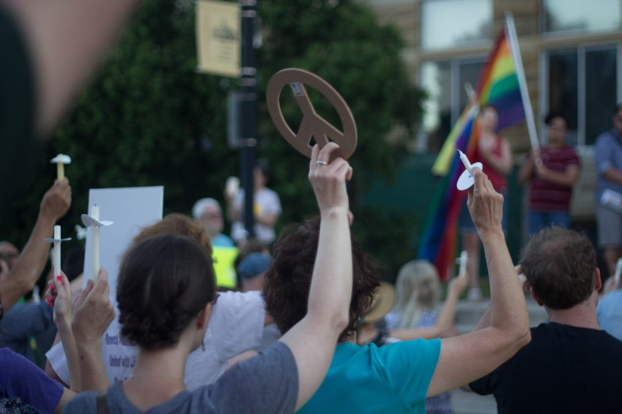 A vigil participant holds up a peace sign as others hold up the flashlights on their phones and their unlit candles in solidarity with the 49 shooting victims in Orlando, on Thursday on the east steps of the Coles County Courthouse.