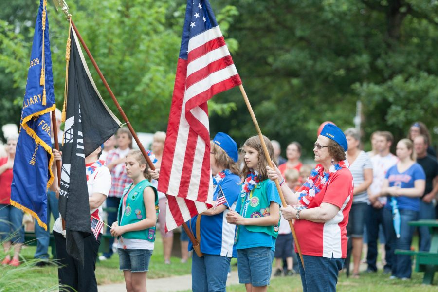 Members of the Girl Scouts and the VFW Ladies Auxiliary bring the flags in at the start of the bell ringing ceremony on Monday at Morton Park.