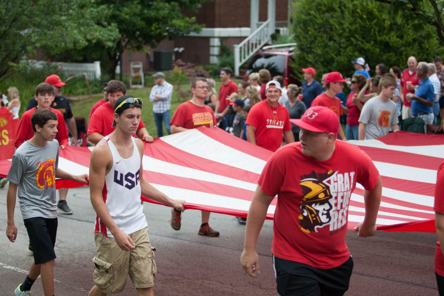 Members of the Charleston High School football team walk the American flag through the parade on Monday.