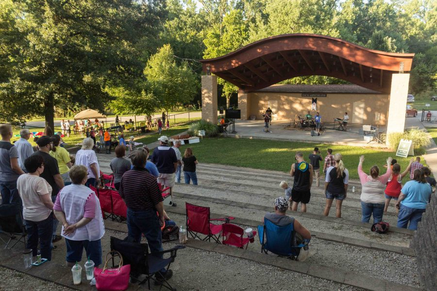 Audience members stand and sing as The Vineyard Church's worship band leads the park in worship songs on Saturday during the Unity Rally at the Daum Amphitheater at Kiwanis Park.