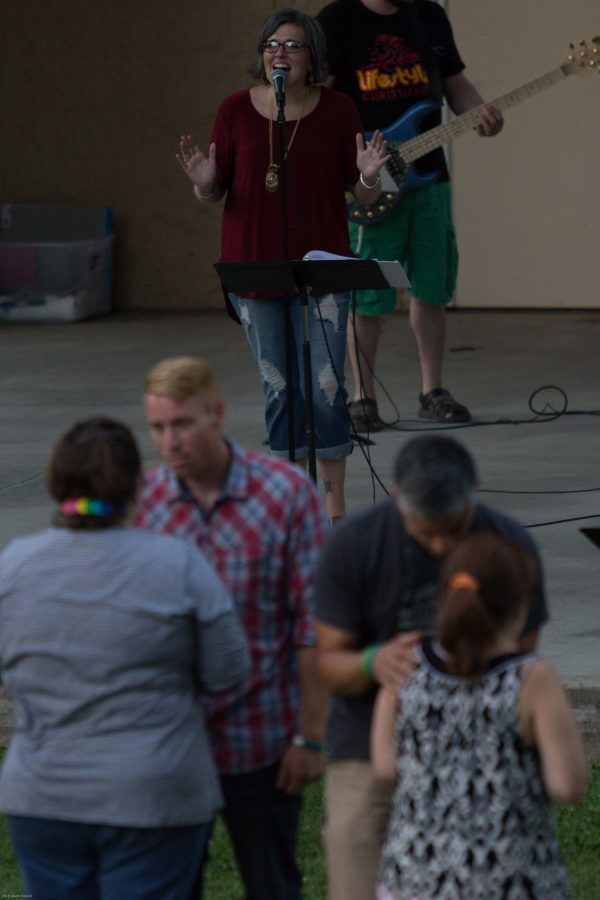 Danelle Jackson, a worship leader at The Vineyard Church, sings as audience members are prayed over during the Unity Rally on Saturday at Daum Amphitheater at Kiwanis Park.