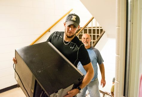 Nick Edges, a psychology major, helps carry a micro-fridge up the stairs at Lawson on Thursday.