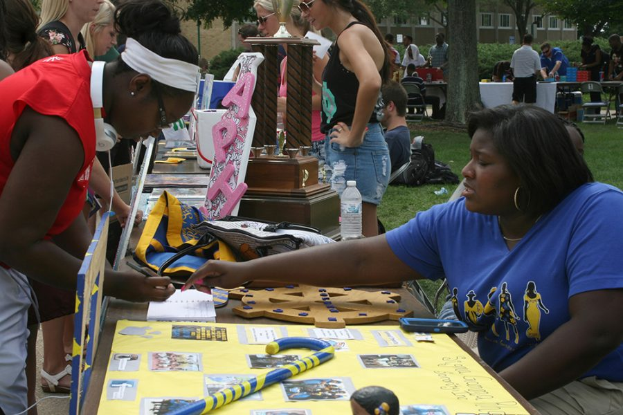 File Photo | The Daily Eastern News Regime Billingsly, a junior athletic training major, explains the sign up sheet for Sigma Gamma Rho Sorority, Inc. to Sarah Ampadu, a senior health studies major, at Panther Palooza on August 27, 2015.