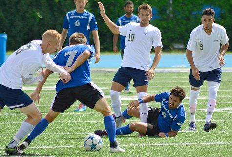 Senior midfielder Fabio Collado watches as teammate Justin Oliver wrestles for the loose ball in a match against University of Illinois-Springfield on Aug. 14 at O'Brien Field.