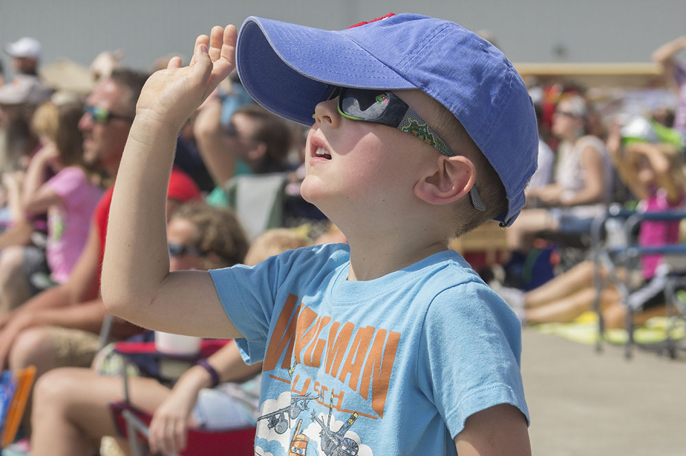 Rowan Faust, a 4-year-old from Philo, Illinois, waves at Wingman Teresa Stokes as she flies past him and his family during the air show at the Coles County Memorial Airport Saturday.