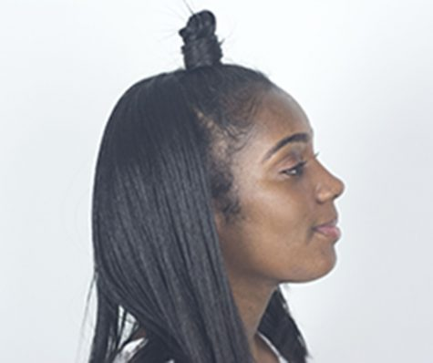 """Kamille Hayslett posing with her """"top knot bun"""" that originated from a hairstyle called bantu knots."""