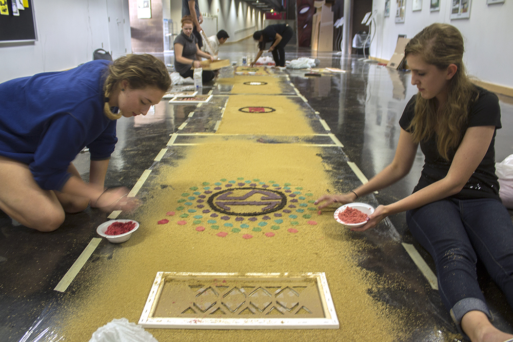 """Kristi Zoubka, a sophomore athletic training major, and Rachel Washburn, a sophomore elementary education major work together on an alfombra for Eastern's Spanish club. """"The freehanding is going a lot better than I thought it would,"""" Zoubka said. """"We're kind of rainbow hombreing it."""""""