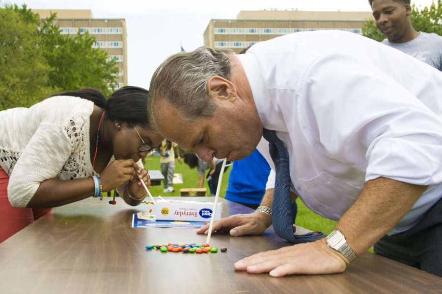 """Hawah Abdulrasaq-coker, sophomore pre med major, completes with President David Glassman in a 30 second 'minute to win-it' game during the 'Go for the Gold!' Prowling with the Prez social. The game required the participants to use straws to move as many m&ms as possible. """"You have to have really good lungs for that,"""" Abdulrasaq-coker said. """"It's not that easy."""" EIU Student Government hosted the olympic themed games from 4 to 6 p.m. in the South Quad on September 15."""