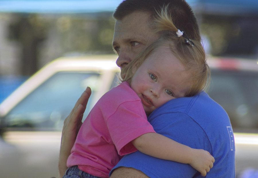 """Cody Galbreath, a resident of Charleston, holds and soothes his daughter Masyn during """"EIU Tailgating"""" Saturday near O'Brien Field."""