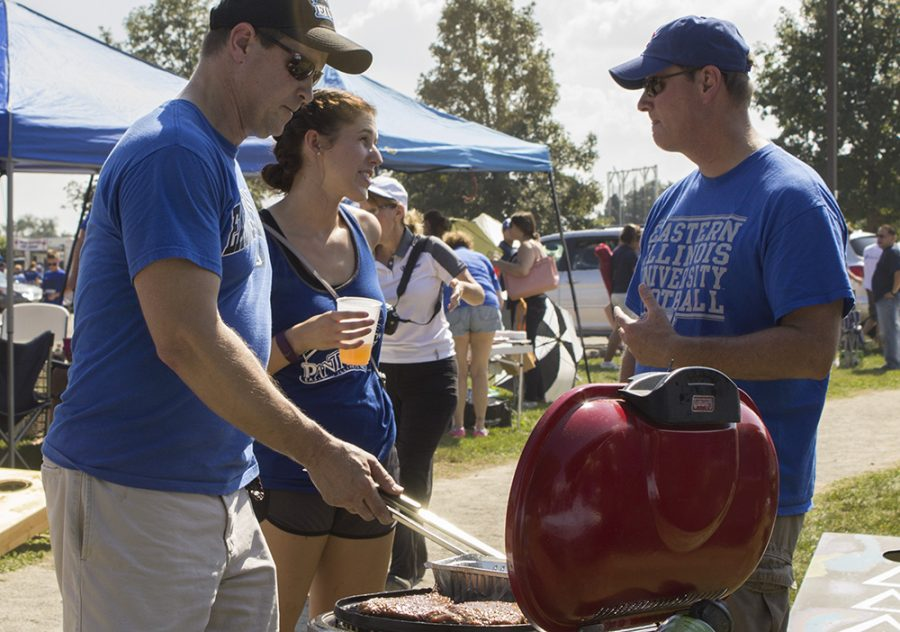 """Marty Fruehe flips flank steaks as his daughter Katie Fruehe, a senior family and consumer sciences major, and her """"cruncle"""" engage in conversation during """"EIU Tailgating"""" Saturday behind O'Brien Field."""