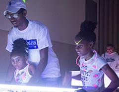 Cassie Buchman | The Daily Eastern News Davion Foster, a sophomore corporate communications major, plays foosball with sisters Allia,5, and Ashila, 9 during Family Funfest Saturday night.