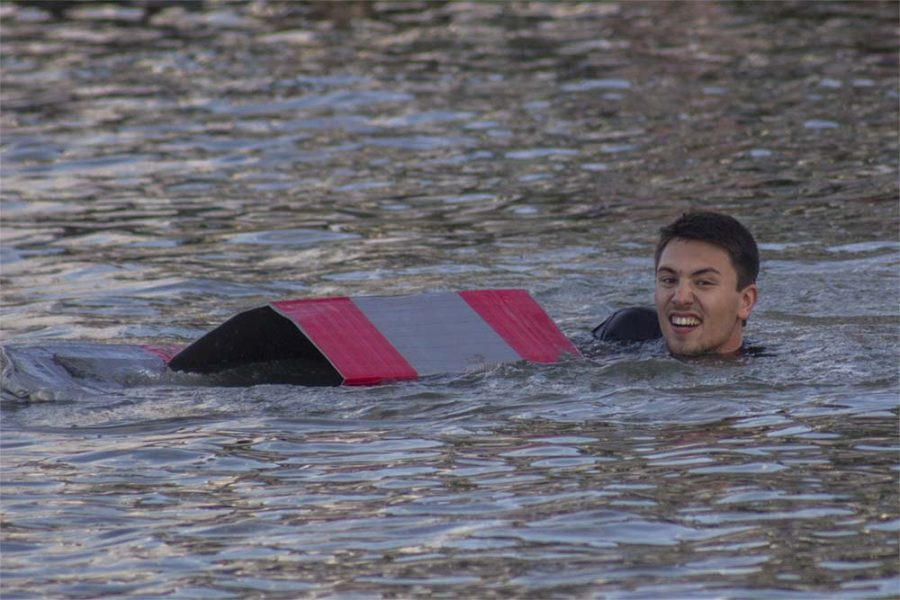 Justin Gunther, a freshman education major, dragging his boat across the campus pond Thursday during the RocFest's Boat Relay.