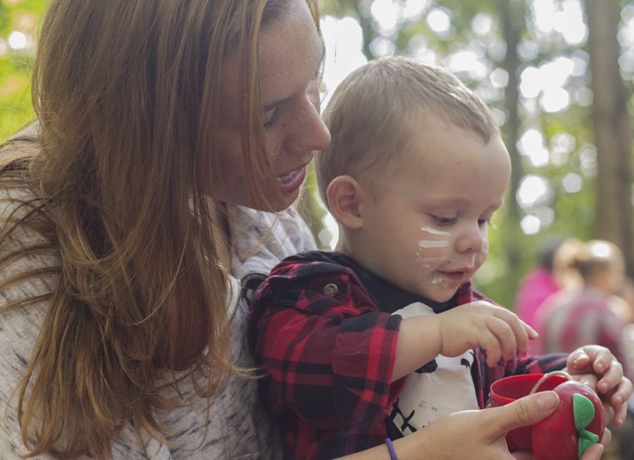 """Mattoon resident Elizabeth Owen helps her one-year-old son Finn O'Dell open a plastic apple he picked out of a bucket as part of a carnival game during the """"Fall Family Festival"""" Saturday at Douglas-Hart Nature Center."""