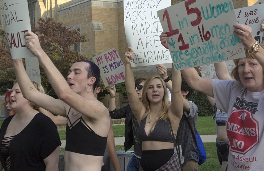"""Alex Wooley, Sophomore 2D art and Spanish major; Siobhan Doherty, freshman sociology major, and Sue Dhermy, a self-employed activist, march and hold signs Thursday during the Slut Walk, hosted by EIU Fem. """"I came to the S.L.U.T. walk last year. It's a really important event,"""" Wooley Said. """"I thought it was important to show my support as a trans-person."""""""