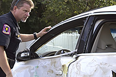Molly Dotson | The Daily Eastern News Lt. Brad Oyer inspects a car that hit a house on Lincoln Avenue after a five-way car accident. The car ran into the house but did not go through it.