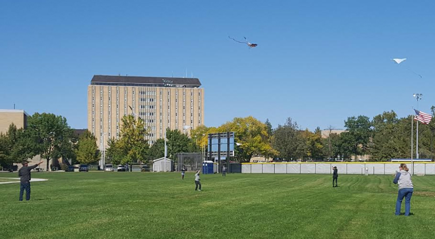 """Families and students fly kites on the Rugby Field Saturday during """"Flying High with EIU.""""  The kites came premade and featured various designs including superheroes, aliens, airplanes and dragons."""