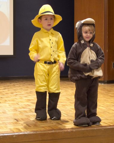 Dressed in the Man in the Yellow Hat and Curious George customes model charleston community children participate in the costume contest during the Annual Kids Fun fest in the grand ballroom of the Martin Luther King Jr. University Union ballroom. During the fest all children model on their Halloween costumes on the stage and the winner earns a bag of candy.