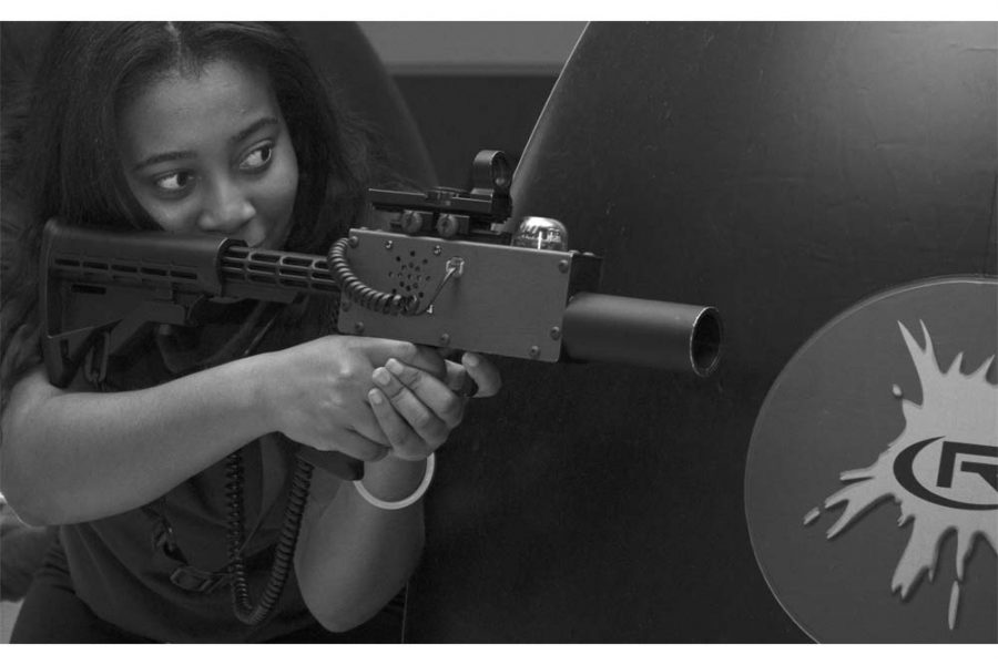 "Christina Brown, a sophomore biology sciences major, aims at the other team during a game of laser tag at the ""Glow Haunted Laser Tag"" event in the University Ballroom of the Martin Luther King Jr. University Union."