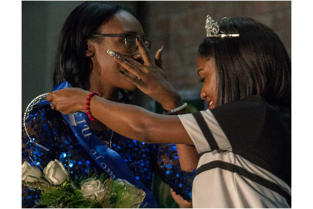 Khayla Kelley-Morton, a junior family and consumer sciences major, wipes tears from her eyes as she is crowned homecoming princess by last year's princess Astoria Griggs-Burns, a senior health adminstration major, during the Homecoming Corination Cerimony Monday in McAfee Gym.